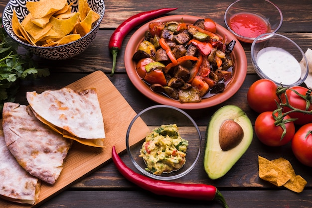 Pita délicieux près de repas parmi les nachos avec des sauces et des légumes Photo gratuit