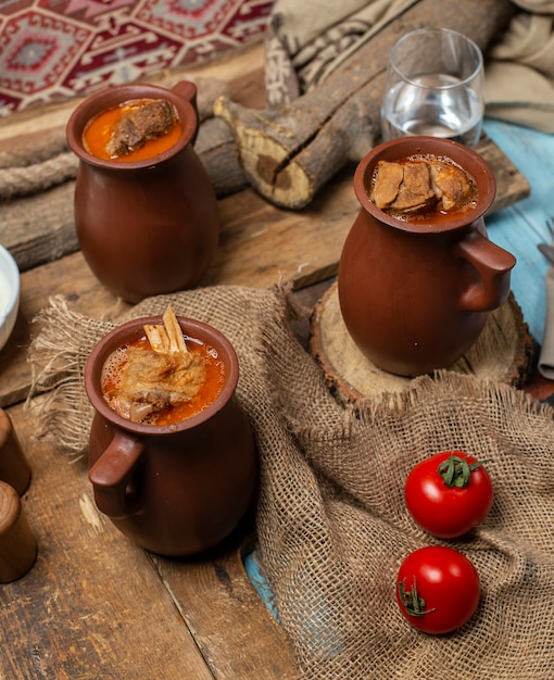 Piti de repas traditionnel azerbaïdjanais dans des tasses en poterie servies avec des tomates. Photo gratuit