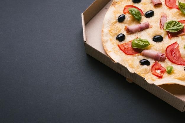 Pizza à angle élevé sur fond noir Photo gratuit