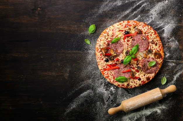 Pizza au basilic, rouleau à pâtisserie, farine sur fond noir foncé, espace copie, vue de dessus Photo Premium