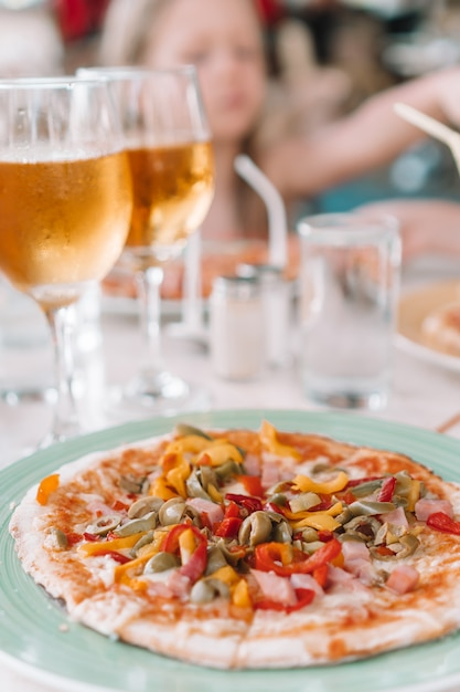 Pizza Au Fromage Mozzarella, Aux Olives, Aux Tomates Fraîches Et Au Pesto. Servi à La Table Du Restaurant Photo Premium
