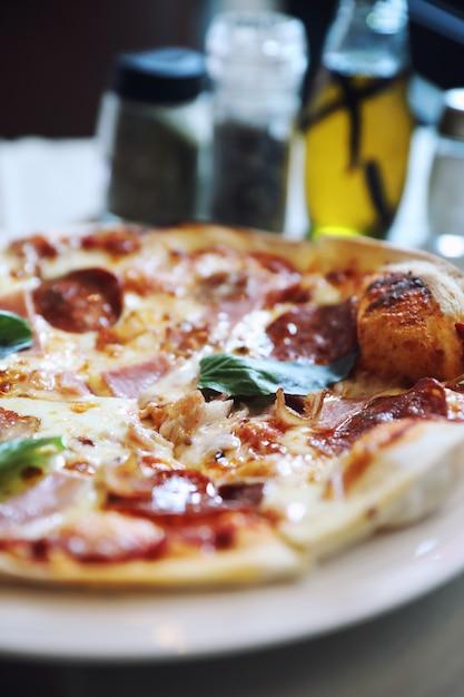 Pizza au jambon et au bacon au pepperoni au fond du restaurant Photo Premium