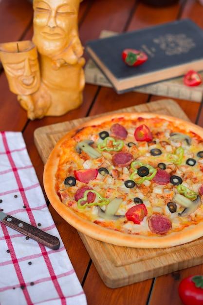 Pizza au pepperoni avec poivrons, tranches de tomates, champignons et olives. Photo gratuit