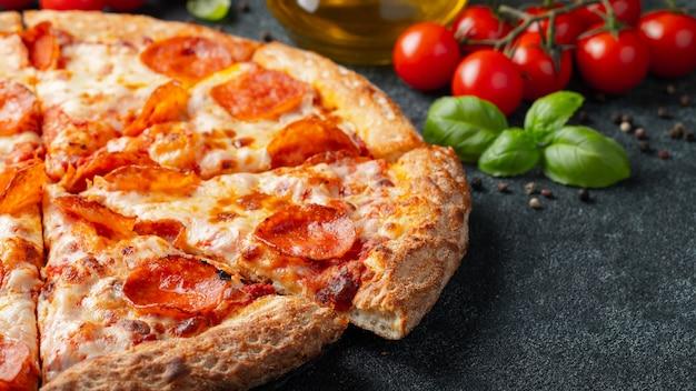 Pizza au pepperoni savoureuse et ingrédients de cuisine tomates basilic sur fond de béton noir Photo Premium
