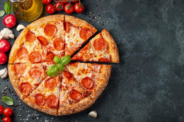 Pizza au pepperoni savoureuse et ingrédients de cuisine Photo Premium