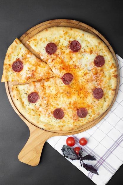 Pizza Au Pepperoni Et Tomates Sur La Table Photo gratuit