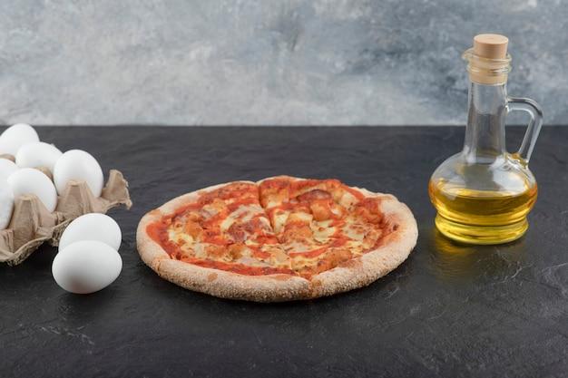 Pizza Au Poulet Buffalo épicé, Huile Et œufs Crus Sur Une Surface Noire. Photo gratuit