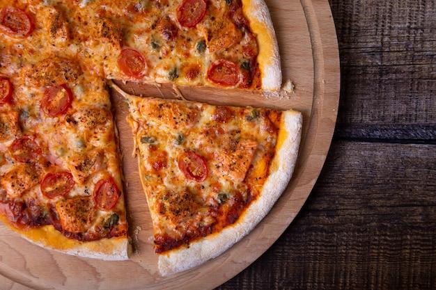 Pizza Au Saumon, Tomates Et Câpres Sur Une Planche De Bois Photo Premium