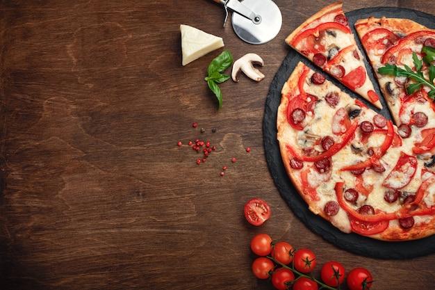 Pizza aux saucisses fumées, fromage, champignons, tomates, poivrons sur une pierre et un plateau en bois brun. Photo Premium
