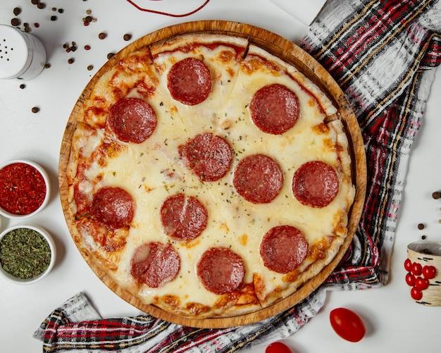 Pizza Aux Saucisses Servie Avec Des Herbes Séchées Photo gratuit