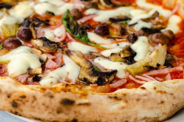 Pizza capricciosa dans un restaurant italien. Photo Premium