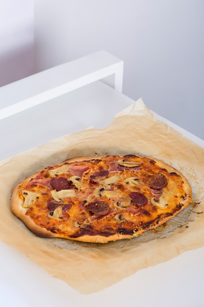 Pizza Cuite Au Four Sur Papier Parchemin Sur La Table Photo Gratuite
