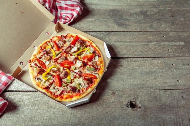 Pizza dans une boîte de livraison sur une table en bois par nappe Photo Premium
