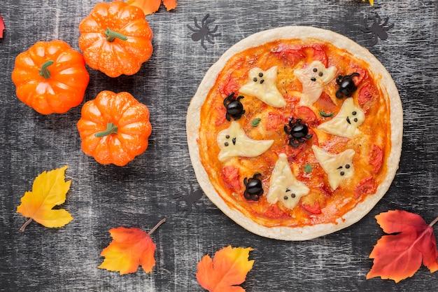 Pizza avec des fantômes effrayants sur le dessus et les citrouilles Photo gratuit