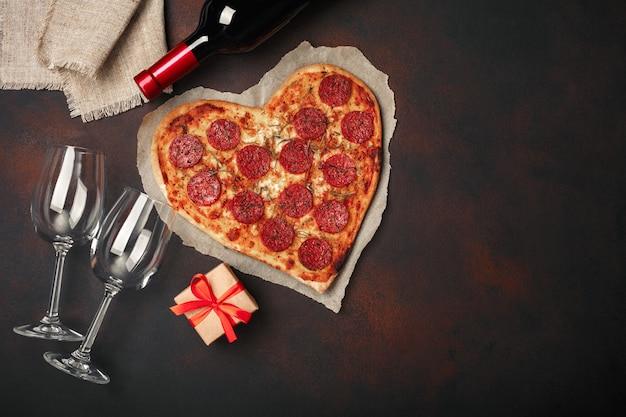 Pizza en forme de coeur avec mozzarella, saucisse, bouteille de vin, deux verres à vin, coffret cadeau sur fond rouillé Photo Premium