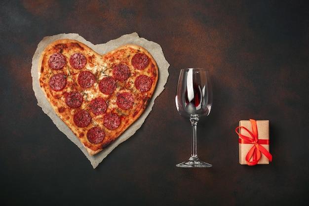 Pizza en forme de coeur avec mozzarella, saucisse, verre à vin, coffret cadeau sur fond rouillé Photo Premium