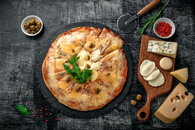 Pizza italienne avec différentes sortes de fromage sur une pierre et un tableau noir craie. cuisine traditionnelle italienne Photo Premium