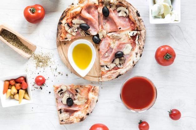 Pizza italienne fraîche avec des ingrédients sur une table en bois blanche Photo gratuit