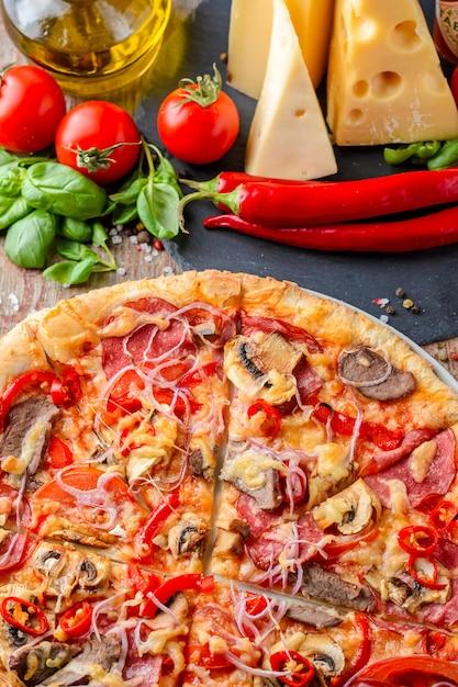 Pizza italienne et ingrédients sur un fond en bois, vue de dessus Photo Premium