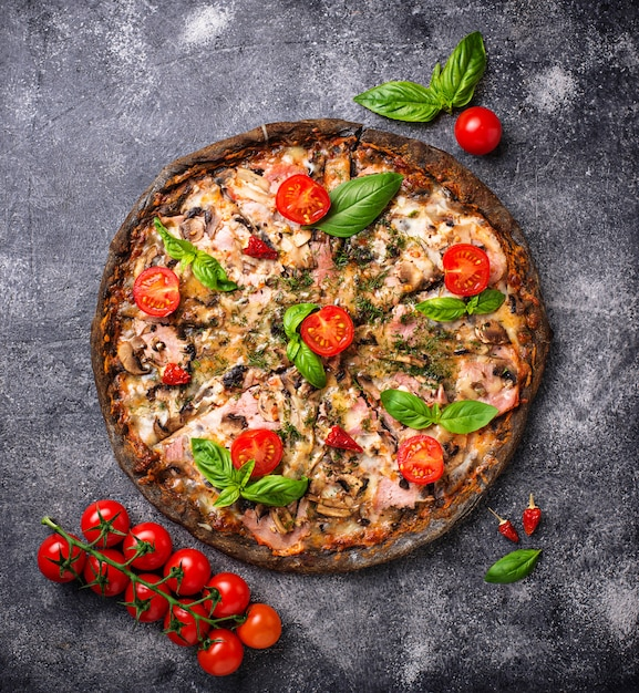 Pizza italienne sur pâte noire. nourriture à la mode Photo Premium