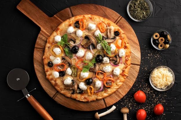 Pizza à La Mozzarella, Aux Olives Et Aux Champignons. Cuisine Italienne. Ingrédients Pour Faire Des Pizzas Sur Fond Noir. Vue De Dessus Concept Pour La Publicité Des Restaurants. Photo Premium