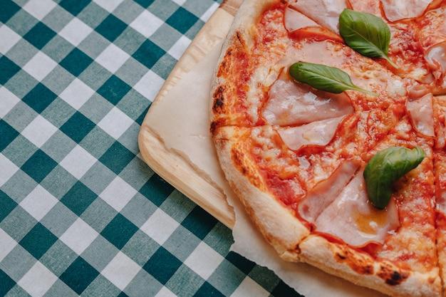 Pizza napolitaine avec jambon, fromage, roquette, basilic, tomates saupoudrées de fromage sur une planche de bois sur une nappe dans une cellule avec une place pour le texte Photo Premium