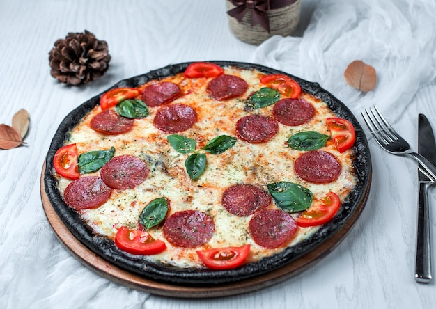Pizza noire au pepperoni, tomate et fromage Photo gratuit
