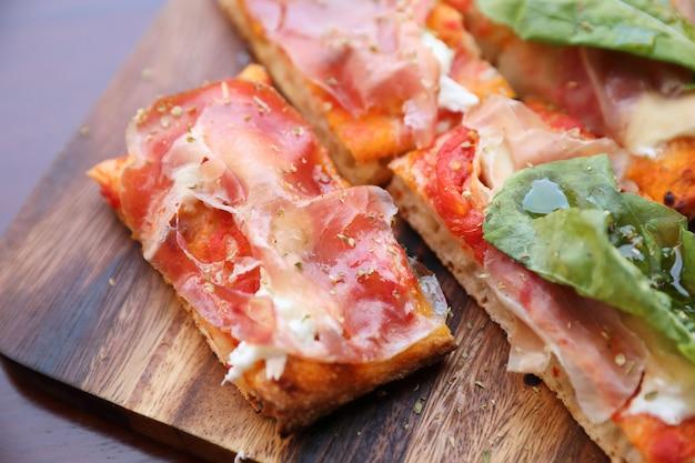 Pizza avec roquette et parmesan de jambon de parme sur un fond en bois foncé se bouchent. nourriture italienne Photo Premium