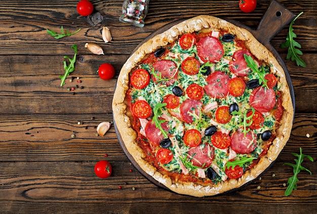 Pizza avec salami, tomates, olives et fromage sur une pâte avec de la farine de blé entier. top vie Photo Premium