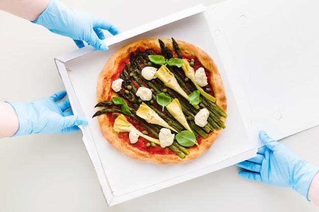 Pizza Végétalienne Aux Asperges Dans Une Boîte Pour La Livraison, La Publicité Ou Le Menu Et Les Mains Dans Des Gants Chirurgicaux Médicaux Pour La Quarantaine Photo Premium