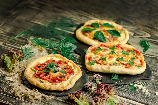 Pizza wariety sur planche de bois et divers ingrédients Photo Premium