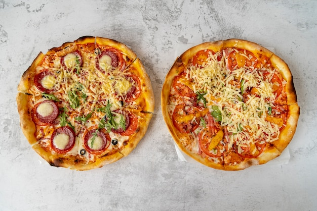 Pizzas vue de dessus sur fond de ciment Photo gratuit