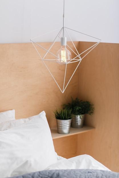 Plafonnier blanc géométrique de style loft avec un fond en bois clair et une ampoule d'edison. Photo gratuit