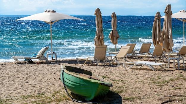 Plage Sur La Côte De La Mer égée Avec Parasols Et Transats, Bateau échoué En Métal De Couleur Verte à Nikiti, Grèce Photo gratuit