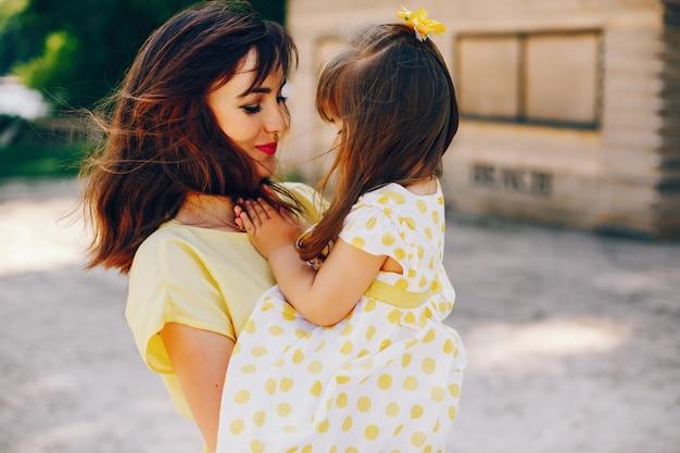 Sur une plage ensoleillée avec du sable jaune, maman se promène dans une robe jaune et sa petite jolie fille Photo gratuit