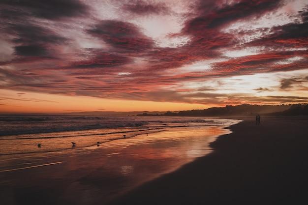Plage Entourée Par La Mer Sous Un Ciel Nuageux Pendant Le Coucher Du Soleil à Brighton En Nouvelle-zélande Photo gratuit