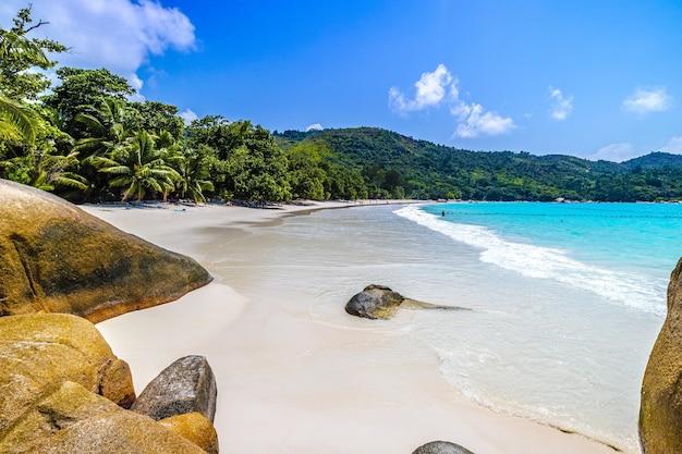 Plage Entourée De Rochers Et De Verdure Sous La Lumière Du Soleil à Praslin Aux Seychelles Photo gratuit