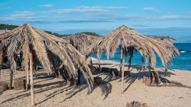 Plage De La Mer égée Avec Des Parasols En Branches De Palmier En Grèce Photo gratuit