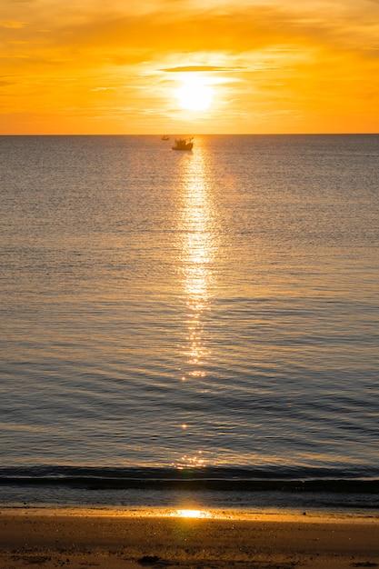 Plage, mer pendant la saison estivale au lever du soleil avec le bateau de pêche silhouette. Photo Premium