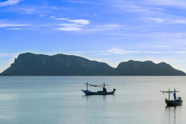Plage, mer pendant la saison estivale au lever du soleil avec petit bateau de pêche. Photo Premium