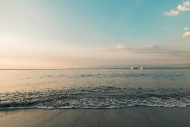 Plage et océan calme aux lumières du coucher du soleil Photo gratuit