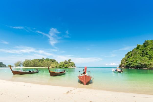 Plage de sable blanc et bateau à longue queue à l'île de kham-tok (koh-kam-tok) Photo Premium
