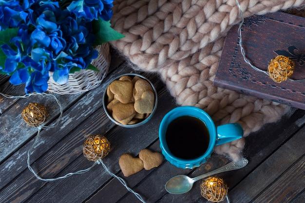 Un plaid, un livre, une tasse de thé bleu, une guirlande et des biscuits Photo Premium