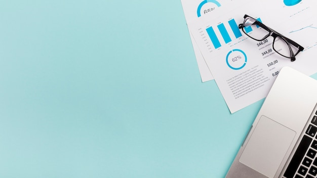 Plan budgétaire, lunettes et ordinateur portable sur fond bleu Photo gratuit