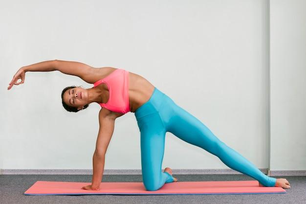 Plan complet femme faisant de l'exercice avec les yeux fermés Photo gratuit