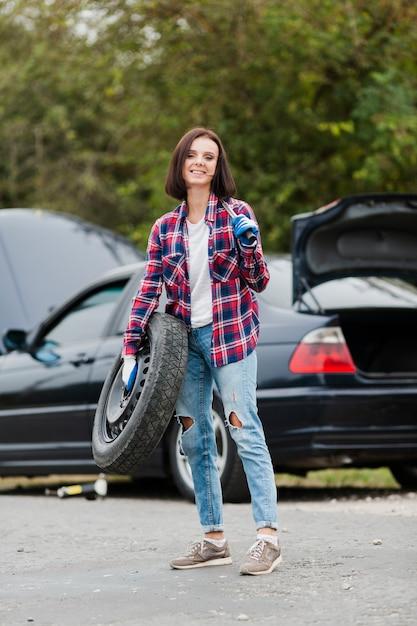 Plan complet d'une femme avec un pneu et une clé Photo gratuit