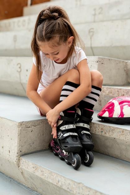Plan complet d'une fille qui met des patins à roues alignées Photo gratuit