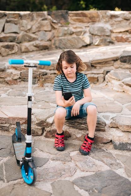 Plan Complet D'un Garçon Regardant Son Téléphone Photo gratuit