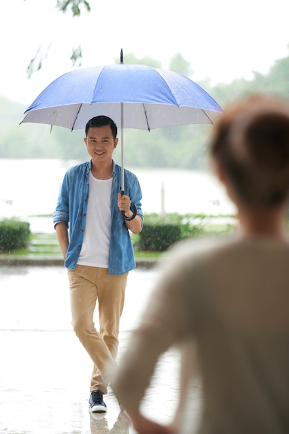 Plan Complet D'un Homme Debout Avec Un Parapluie Sous La Pluie, Attendant Sa Date Pour Venir Photo gratuit