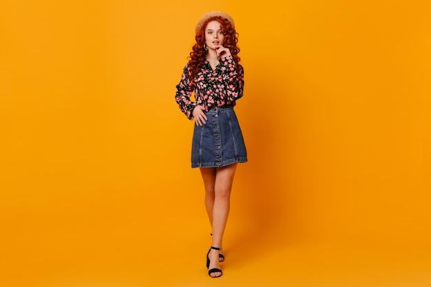 Plan Complet D'une Jeune Femme Mince En Jupe En Jean élégante, Chemise Avec Des Pics à Fleurs Et Chapeau En Studio Orange. Photo gratuit
